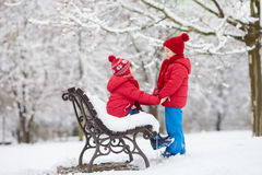 Two adorable children, boy brothers, playing in a snowy park, ho Royalty Free Stock Images