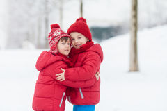 Two adorable children, boy brothers, playing in a snowy park Stock Photos