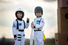 Two adorable children, playing in park on sunset, dressed like a. Two adorable children, boy brothers, playing in park on sunset, dressed like astronauts Stock Photography