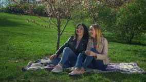 Two adorable diverse girls resting in blooming park stock footage