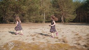 Two girls are running on sand in a summer forest. Two adorable girls in dresses are running on sand in a summer forest stock footage