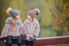 Two adorable girls in forest at warm sunny autumn day Royalty Free Stock Photo