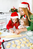 Two adorable girls and mother baking Christmas cookies Stock Photo