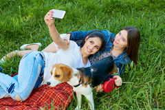 Two adorable girls posing with their dog   in park. Royalty Free Stock Photos
