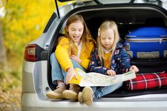 Two adorable girls sitting in a car trunk before going on vacations with their parents. Two kids looking forward for a road trip o. R travel. Autumn break at Stock Photos