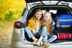Two adorable girls sitting in a car trunk before going on vacations with their parents. Two kids looking forward for a road trip o. R travel. Autumn break at Royalty Free Stock Photos