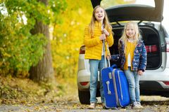 Two adorable girls with a suitcase going on vacations with their parents. Two kids looking forward for a road trip or travel. Autu. Mn break at school. Family Royalty Free Stock Photo
