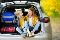 Two adorable girls with a suitcase going on vacations with their parents. Two kids looking forward for a road trip or travel. Autu Stock Photo