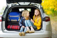 Two adorable girls with a suitcase going on vacations with their parents. Two kids looking forward for a road trip or travel. Autu. Mn break at school. Family Stock Photo