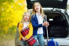 Two adorable girls with a suitcase going on vacations with their parents. Two kids looking forward for a road trip or travel. Autu. Mn break at school. Family Stock Image