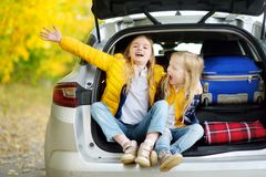 Two adorable girls with a suitcase going on vacations with their parents. Two kids looking forward for a road trip or travel. Autu. Mn break at school. Family Royalty Free Stock Image