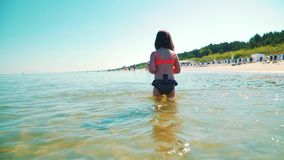 Two adorable girls in swimsuits are playing in the sea. In summer stock video