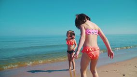 Two adorable girls in swimsuits are playing in the sea. In summer stock footage