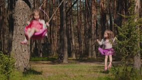 Two girls are swinging on swings in the forest stock video