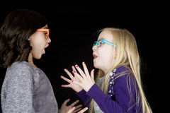 Two adorable girls wearing funky glasses drama in expression Royalty Free Stock Photos