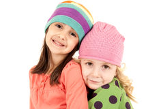 Two adorable girls wearing winter hats hugging Stock Image