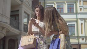 Two adorable happy girlfriends after shopping with shopping bags texting on the cellphone in front of beautiful. Two happy girlfriends after the shopping with stock video footage