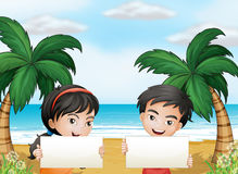 Two adorable kids at the beach with empty signboards Stock Image