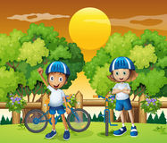 Two adorable kids biking Stock Images