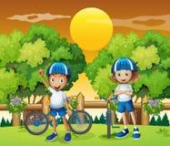Two adorable kids biking Stock Images
