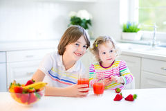 Two adorable kids having fruit for breakfast drinking juice Stock Image