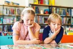 Little kids portrait. Two adorable kids, little girl and her brother reading book in a library Stock Photography