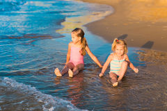 Two adorable kids playing in the sea on a beach Stock Image