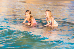 Two adorable kids playing in the sea on a beach Stock Photos