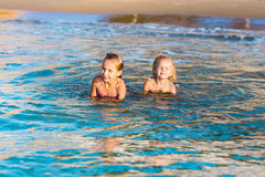 Two adorable kids playing in the sea on a beach Stock Photo