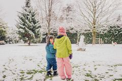 Two adorable kids playing together. In snow park, wearing warm winter clothes, back view Stock Images