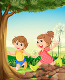 Two adorable kids playing under the tree Royalty Free Stock Image