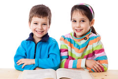 Two adorable kids reading the book Stock Images