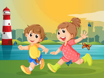 Two adorable kids running with butterflies Stock Images