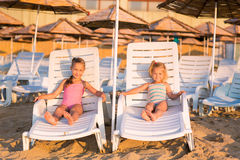 Two adorable kids sunbathing on a beach Royalty Free Stock Image