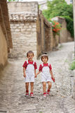 Two adorable kids, walking on the street, smiling at camera Royalty Free Stock Photography