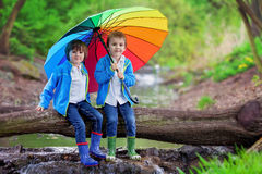 Two adorable little boy, brothers, sitting on a wooden trunk on stock photography