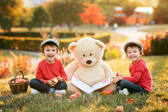 Two adorable little boys with his teddy bear friend in the park. On sunset, nice back light Stock Image