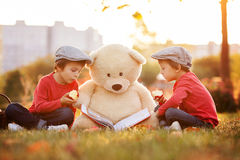 Two adorable little boys with his teddy bear friend in the park Stock Photo