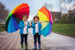 Two adorable little boys, walking in a park on a rainy day, play Royalty Free Stock Photography