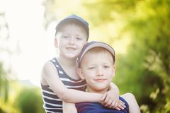 Two adorable little brothers laughing and hugging on sunny summer day Royalty Free Stock Photography