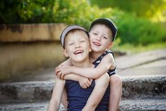Two adorable little brothers laughing and hugging on warm and sunny  day Royalty Free Stock Photo