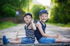 Two adorable little brothers sitting on stone on warm and sunny Stock Photos