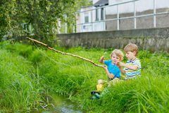 Two adorable little friends  fishing with selfmade rod Royalty Free Stock Image