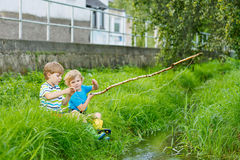 Two adorable little friends  fishing with selfmade rod Royalty Free Stock Photos