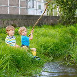 Two adorable little friends  fishing with selfmade rod Royalty Free Stock Photo
