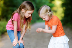 Two adorable little girl catching babyfrogs Royalty Free Stock Image