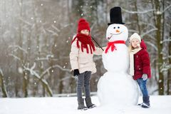 Two adorable little girls building a snowman together in beautiful winter park. Cute sisters playing in a snow. Royalty Free Stock Photos