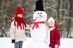 Two adorable little girls building a snowman together in beautiful winter park. Cute sisters playing in a snow. Winter activities for kids Royalty Free Stock Images