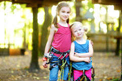 Two adorable little girls enjoying their time in climbing adventure park on warm and sunny summer day Stock Photography