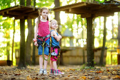 Two adorable little girls enjoying their time in climbing adventure park on warm and sunny summer day Stock Photos